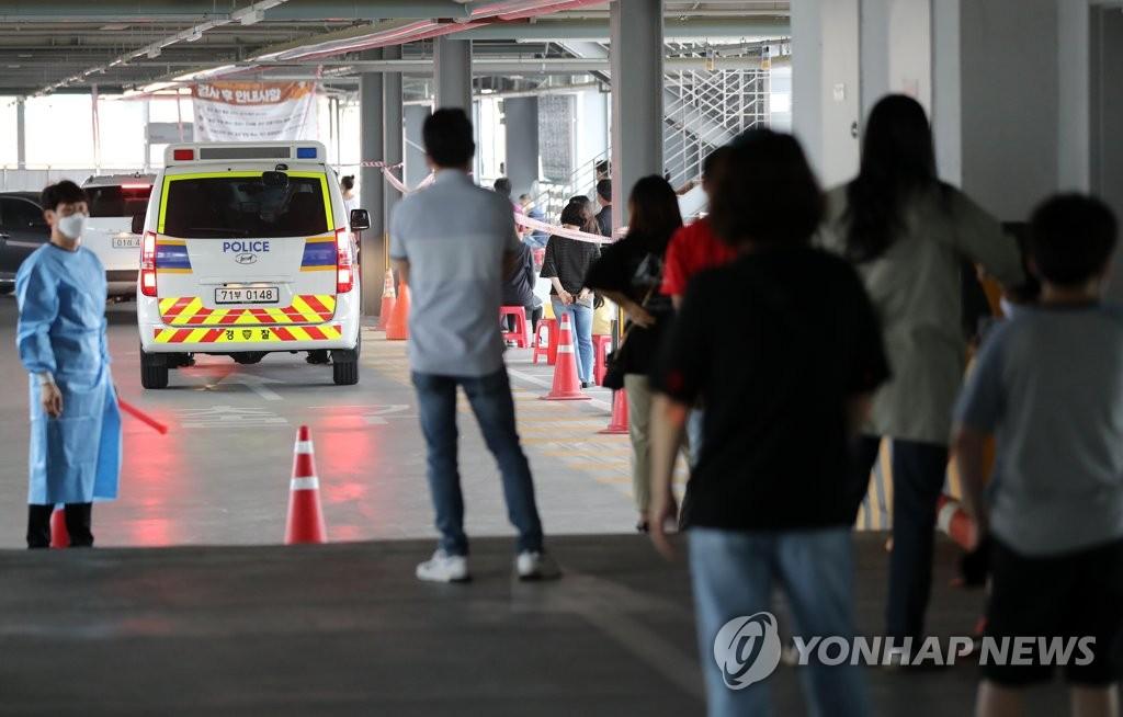 资料图片:6月29日,在位于光州市的一处筛查诊所,市民们排队待检。 韩联社