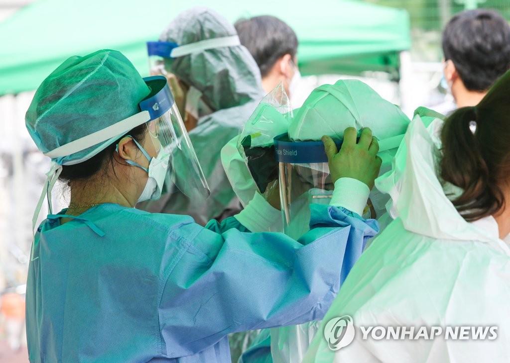 资料图片:7月2日,在位于大田市的一所小学,医疗人员穿防护服准备为小学生进行新冠病毒检测。 韩联社
