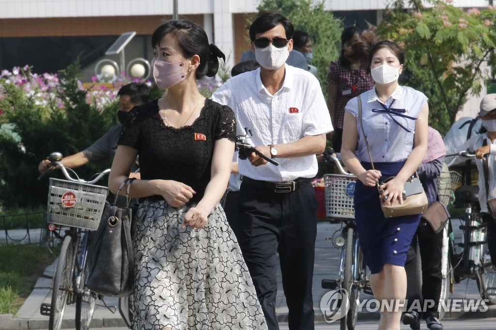 资料图片:平壤居民戴口罩出行。 韩联社