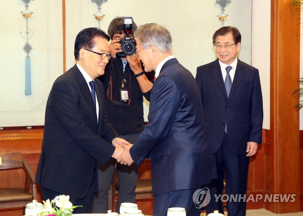 资料图片:朴智元(左)与文在寅握手致意。 韩联社