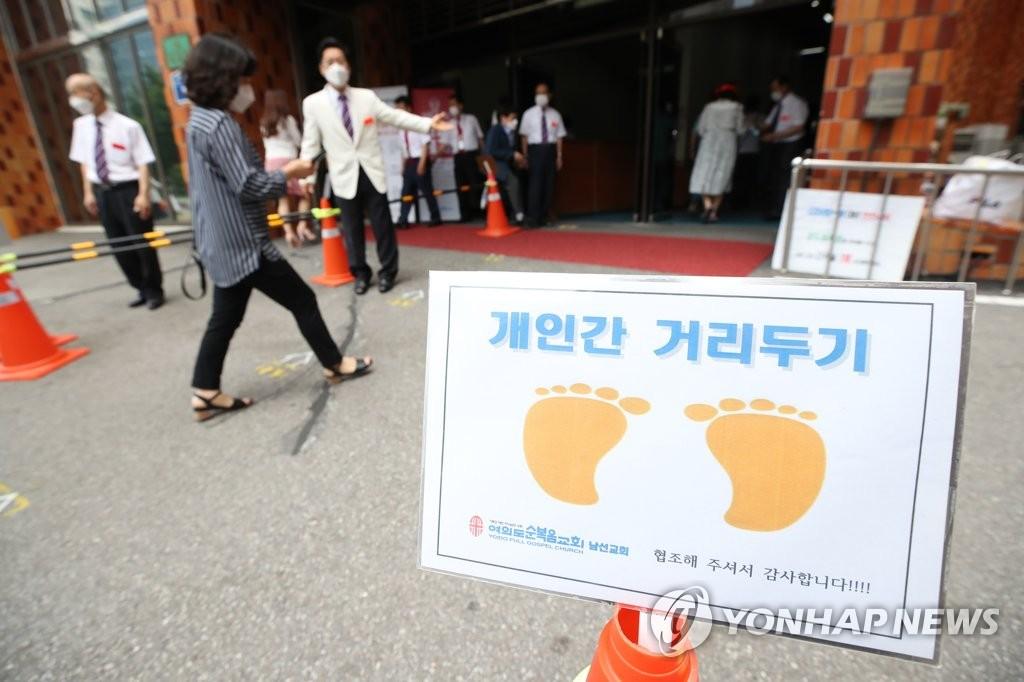 资料图片:7月5日,在首尔市汝矣岛,教徒在进入教堂前保持社交距离。 韩联社