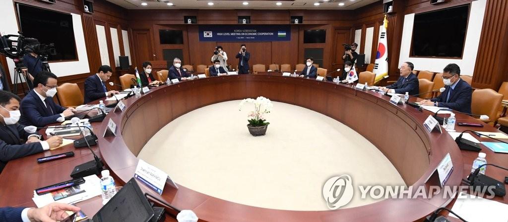 7月7日下午,在中央政府首尔办公楼,洪楠基(右二)和乌穆尔扎科(左三)举行会晤。 韩国企划财政部供图(图片严禁转载复制)