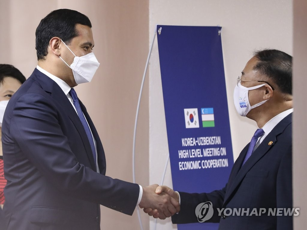 7月7日下午,在中央政府首尔办公楼,洪楠基(右)和乌穆尔扎科举行会谈前握手致意。 韩联社