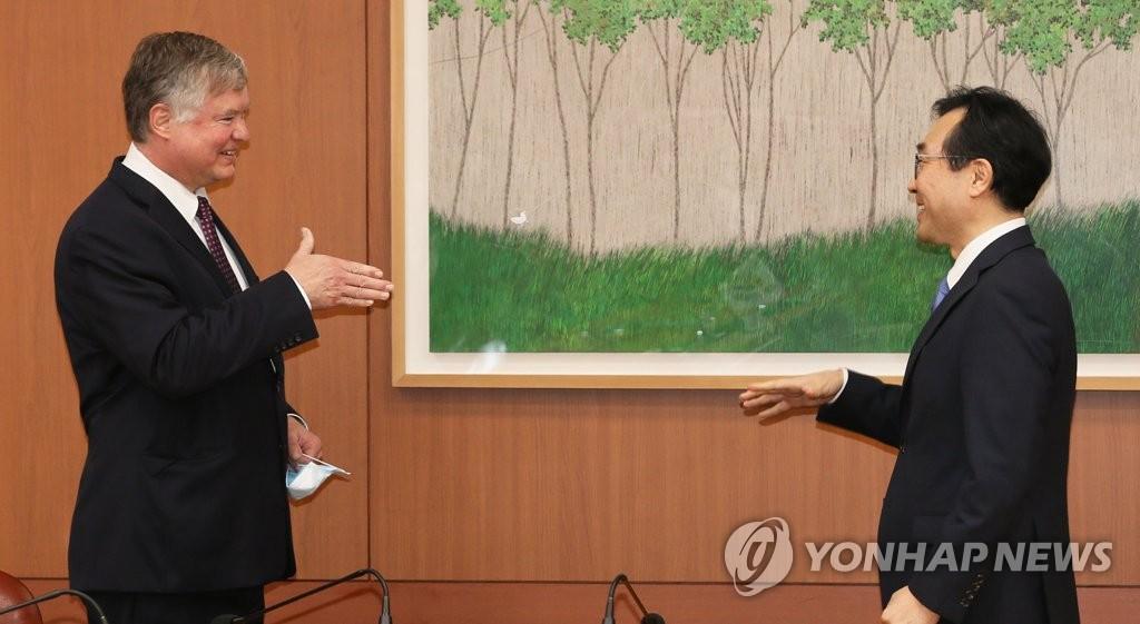资料图片:7月8日上午,在首尔市的韩国外交部,李度勋和比根通过非接触式握手保持防疫距离。 韩联社/摄影记者团供图(图片严禁转载复制)