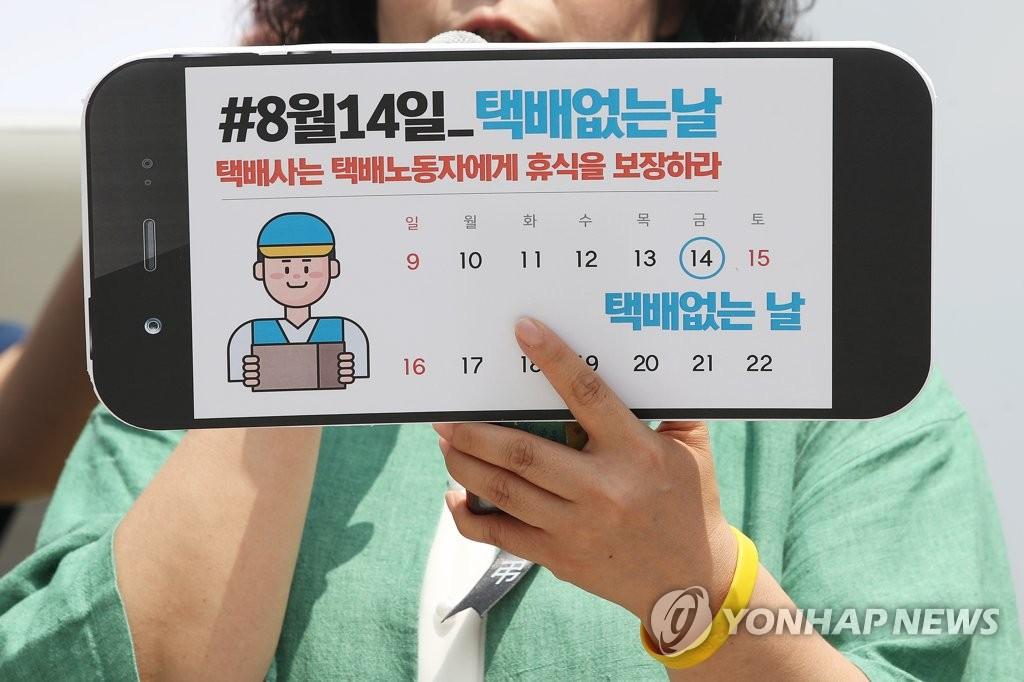 资料图片:7月9日,在首尔光化门广场举行的记者会上,参加人员举牌敦促将8月14日指定为无快递日。 韩联社