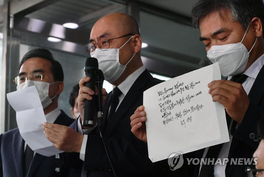 资料图片:7月10日,在设于首尔大学医院的已故首尔市长朴元淳的灵堂前,首尔市长秘书室长高汉锡(音,居中)公开朴元淳遗书。 韩联社