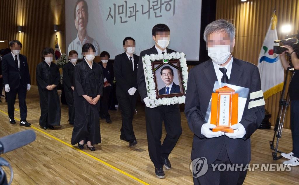 7月13日上午,在首尔市政厅多功能厅,遗属捧着朴元淳的灵牌和遗像退场。 韩联社/摄影记者团供图(图片严禁转载复制)