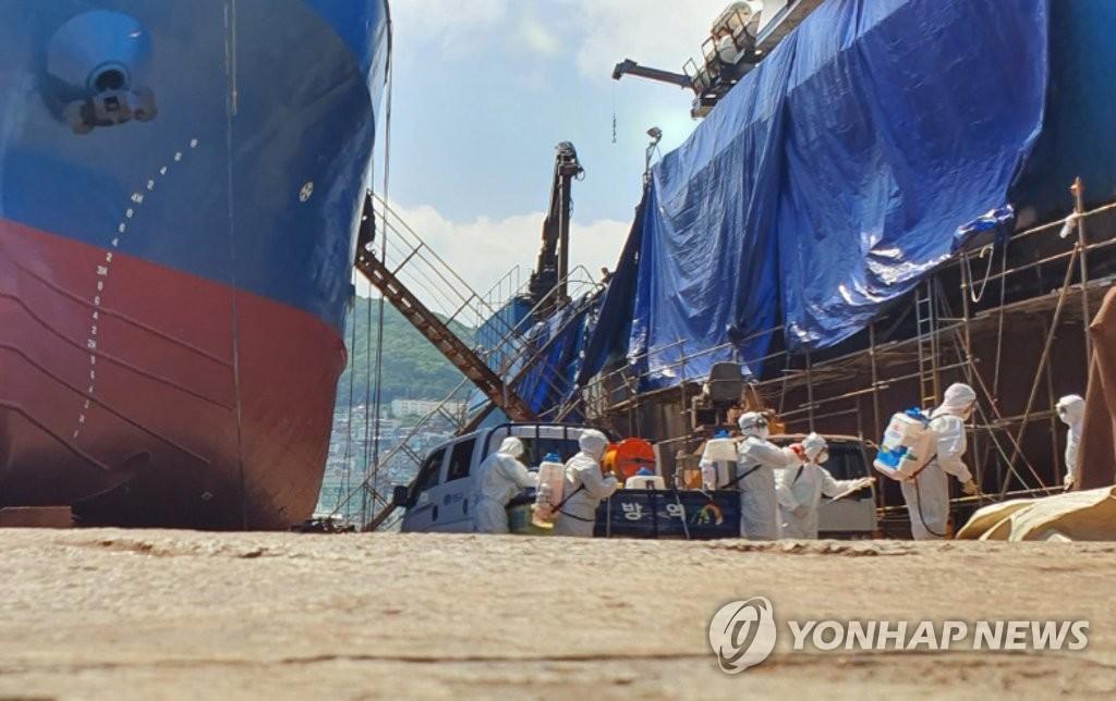 工作人员对出现确诊病例的俄籍船舶进行防疫消毒。 韩联社