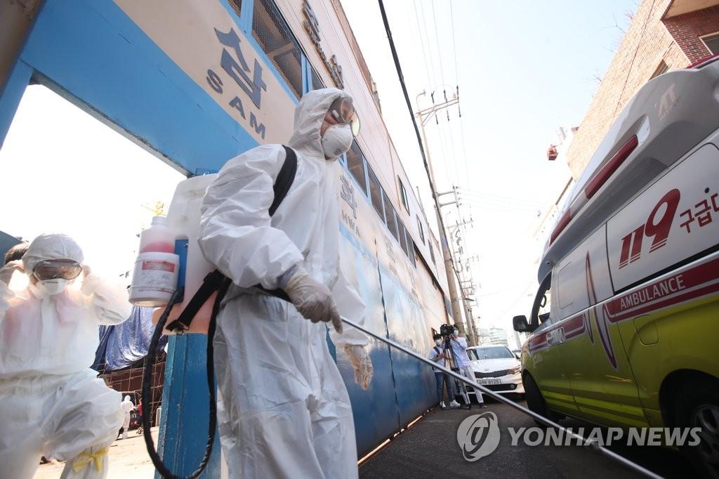 资料图片:防疫人员在进行防疫消毒。 韩联社