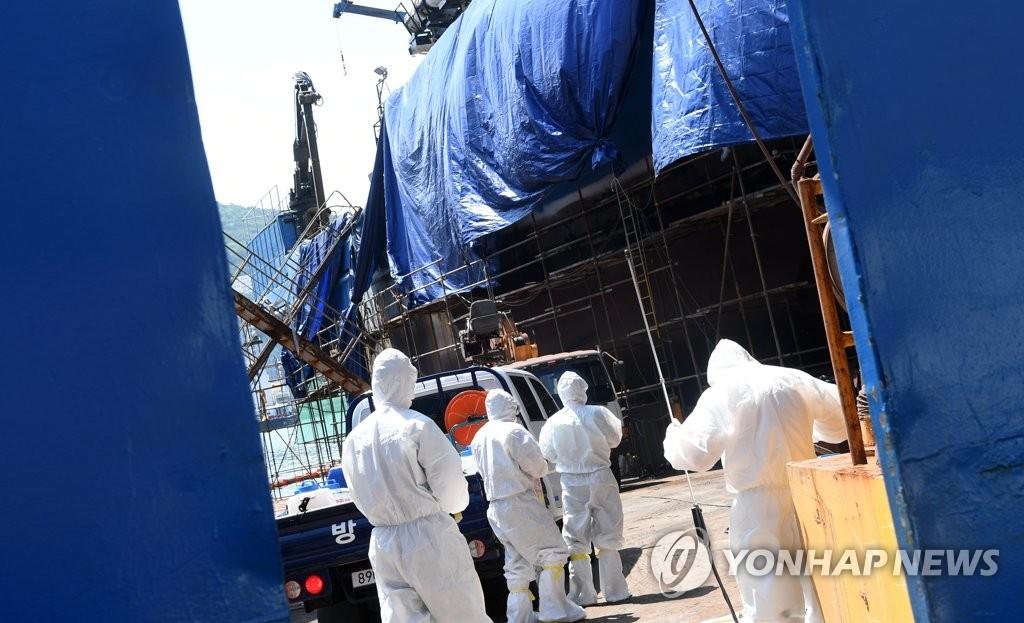 资料图片:防疫部门人员在釜山港进行防疫消毒。 韩联社