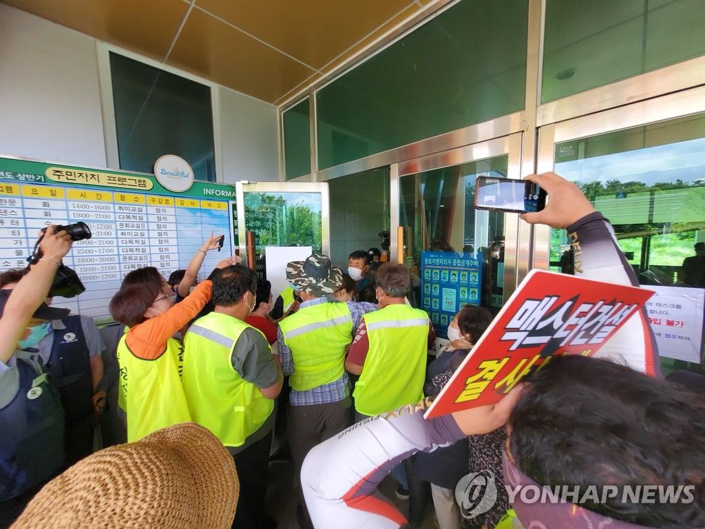 7月24日,在庆州市甘浦邑福利会馆前,反对增设月城核电站乏燃料临时存储库的居民与前来疏散人群的警察形成对峙。 韩联社