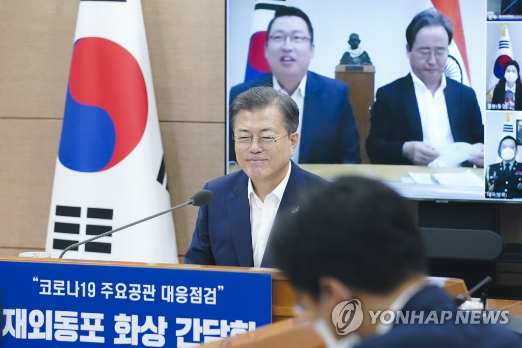 7月24日,在首尔外交部综合状况室,文在寅在旅外同胞视频座谈会上同驻印度大使申凤吉(屏幕中右)和当地韩侨亲切对话。 韩联社