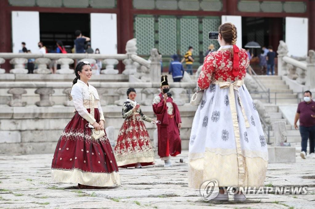 资料图片:在首尔钟路区的景福宫,外国游客们身穿韩国传统服饰边拍照边游览。 韩联社