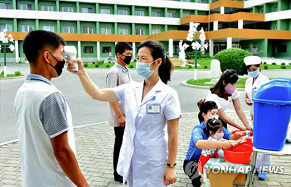 资料图片:7月27日,朝鲜居民正在测体温、洗手。 韩联社/《劳动新闻》官网截图(图片严禁转载复制)