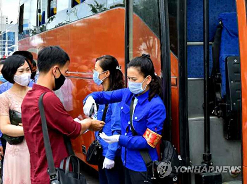 资料图片:朝鲜劳动党机关报《劳动新闻》7月27日报道,朝鲜全境火车站、长途汽车站、各道边界等重要地点加强防疫防控工作,对流动人员和器材实施病毒检测和消毒。图为乘客们乘车前接受测温。 韩联社/《劳动新闻》官网截图(图片仅限韩国国内使用,严禁转载复制)
