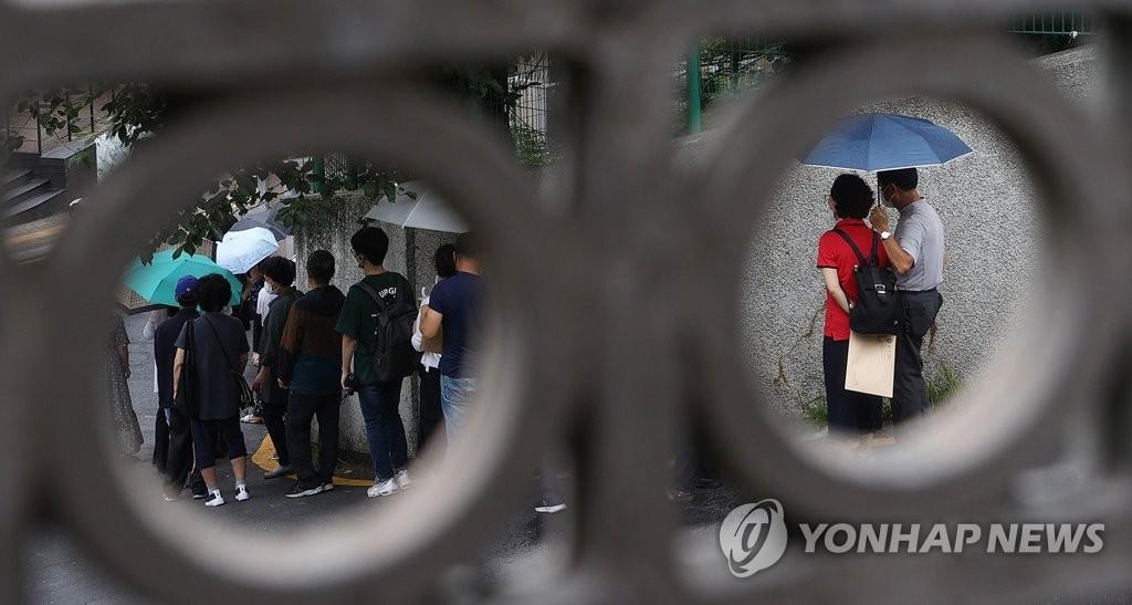 资料图片:7月28日上午,在首尔中区中国驻韩大使馆领事部门前,前来办理签证业务的人们排成长龙。 韩联社