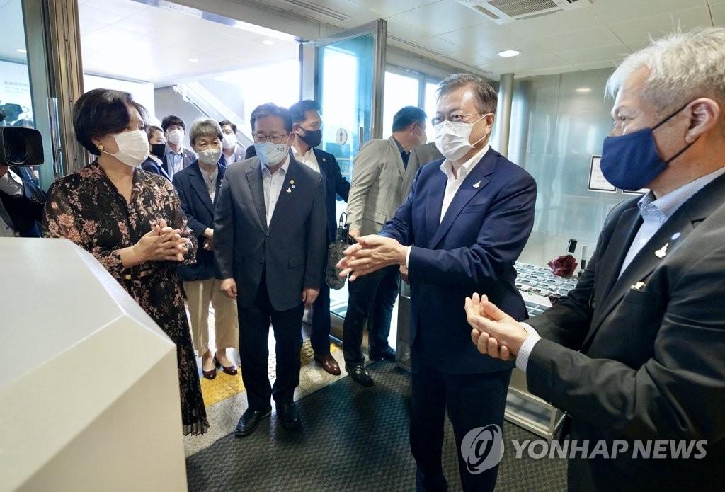 7月30日,韩国总统文在寅(右二)携夫人金正淑女士(左)前往国立中央博物馆观看大型国宝展览。图为文在寅一行在入口处进行常规手部消毒。 韩联社