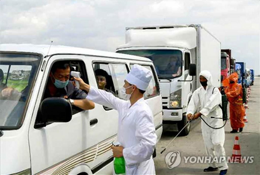 图为朝鲜防疫工作人员为过往车辆司机测温防疫。 韩联社/《劳动新闻》官网截图(图片仅限韩国国内使用,严禁转载复制)