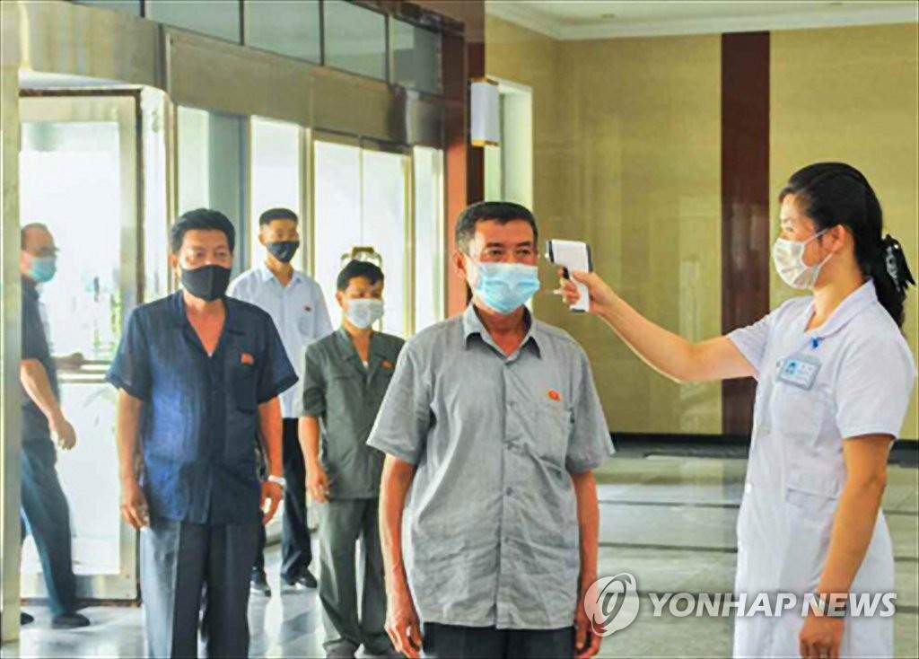资料图片:朝鲜防疫工作人员(右一)在一楼宇门口为准备进入该楼的人员进行测温。 韩联社/《劳动新闻》官网截图(图片仅限韩国国内使用,严禁转载复制)