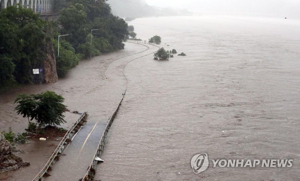 8月3日,江原道春川市北汉江因暴雨泛滥,周围的公路被洪水淹没。 韩联社