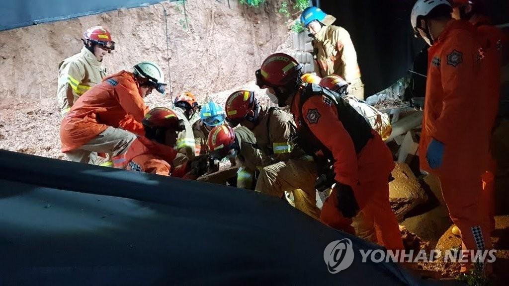8月3日,在京畿道平泽市一家工厂被沙土掩埋,消防人员展开搜救工作。 韩联社/京畿消防灾难本部供图(图片严禁转载复制)