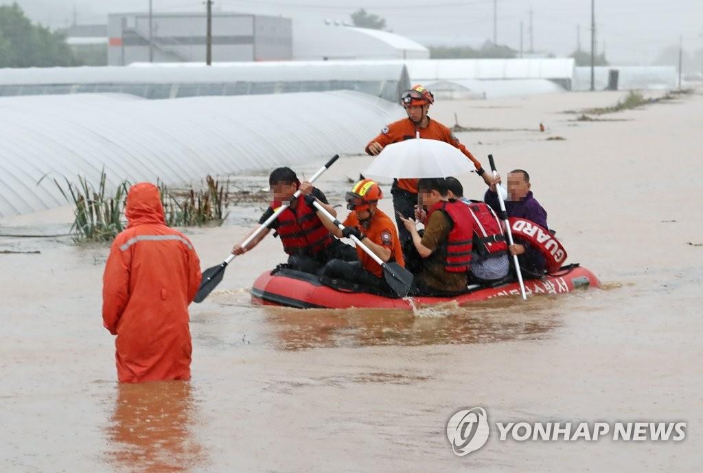 资料图片:8月3日上午,忠清南道天安市的某公路被水淹没。消防人员用橡皮艇救助当地居民。 韩联社