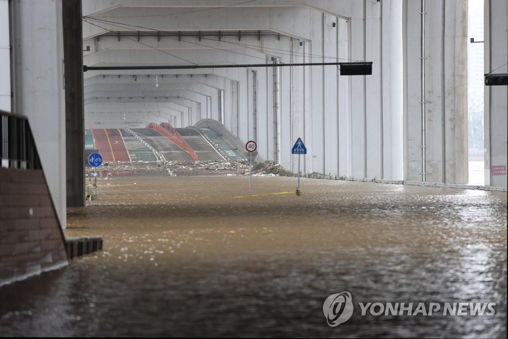 资料图片:8月4日上午,受暴雨影响,汉江水位暴涨导致桥梁被水淹没。 韩联社