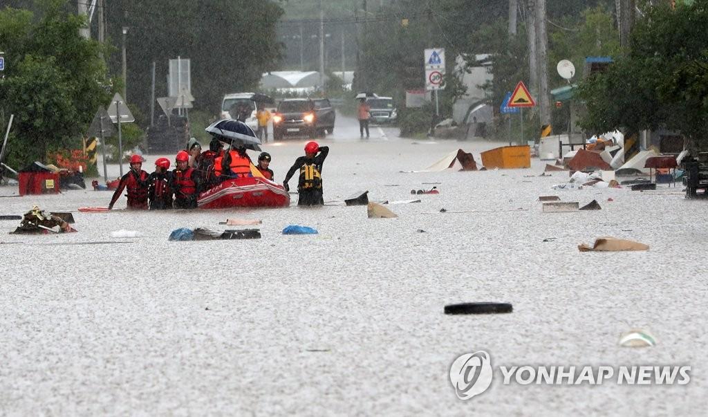 资料图片:8月5日上午,江原道铁原郡金化邑一带被水淹没,消防人员用橡皮艇营救当地居民。 韩联社