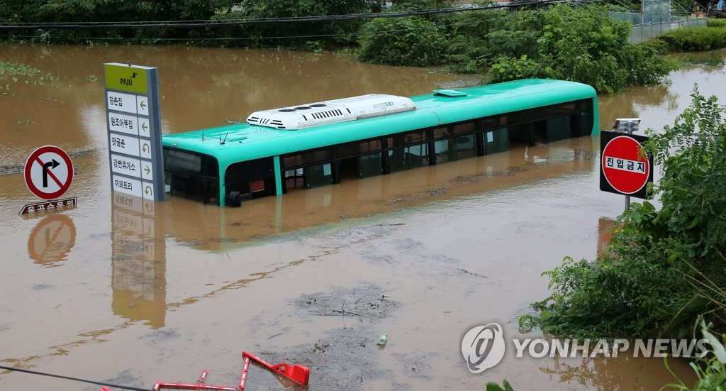资料图片:8月6日,京畿道坡州市降下暴雨,导致当地河水暴涨,一辆公交车被河水淹没。 韩联社