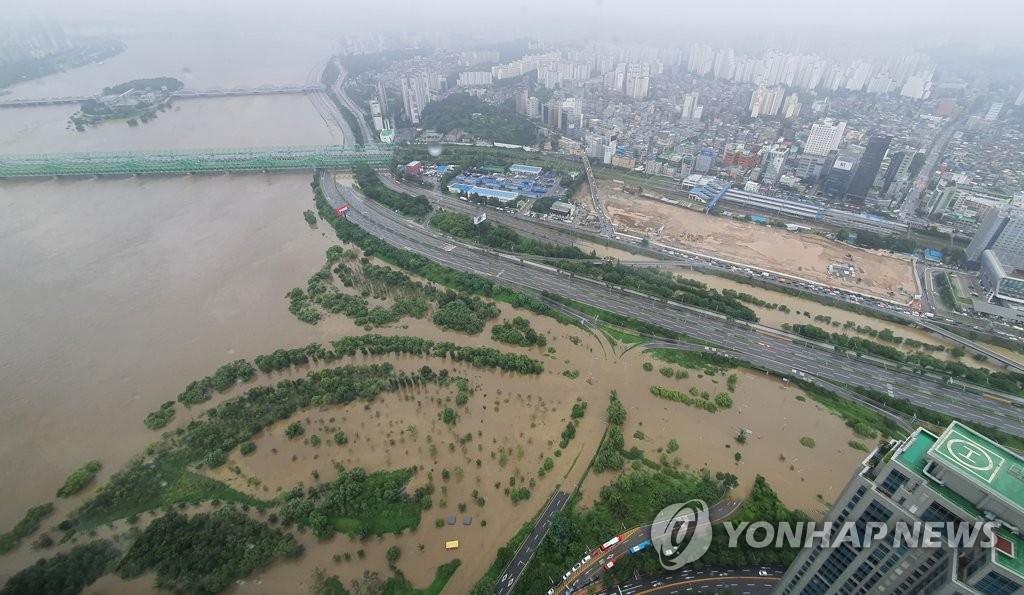 资料图片:8月6日,受暴雨影响,汉江铁桥附近的路面被江水淹没。 韩联社