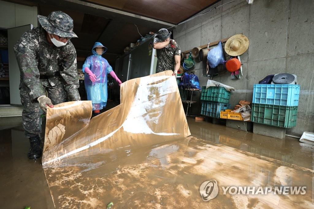 资料图片:8月6日,在江原道铁原郡金化邑生昌里村,抢险救灾人员修复一处遭洪水侵害的房屋。 韩联社