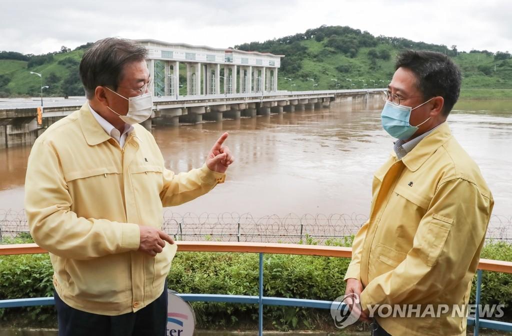 8月6日下午,在京畿道涟川郡郡南水位调节坝,文在寅与水资源公社负责人交谈。 韩联社