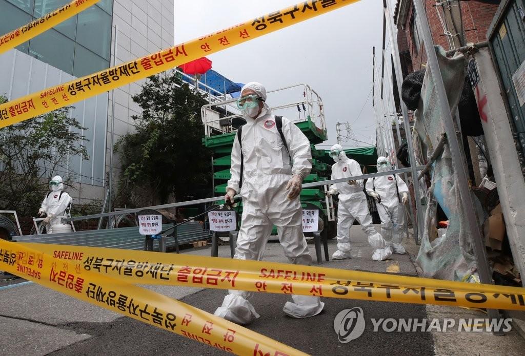 """资料图片:8月14日,防疫人员在发生群聚性感染事件的首尔市""""爱第一教会""""进行防疫消毒。 韩联社"""
