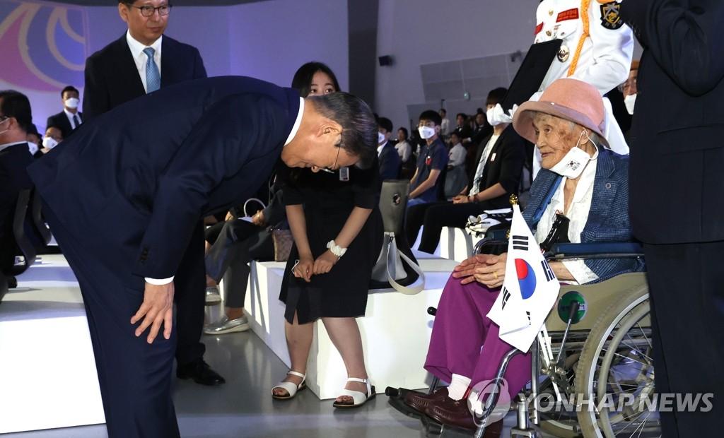 8月15日,在首尔东大门设计广场,韩国总统文在寅出席光复节庆祝仪式。图为文在寅(左)向爱国志士遗属鞠躬致敬。 韩联社