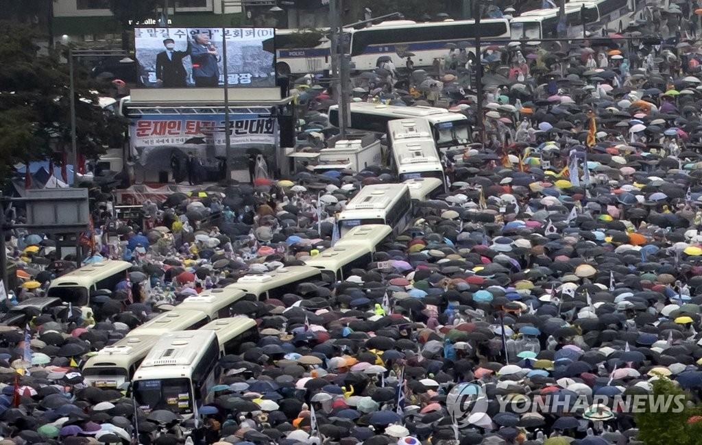资料图片:8月15日下午,在首尔市钟路区东和免税店,爱第一教会牧师向反政府集会人群发言。 韩联社