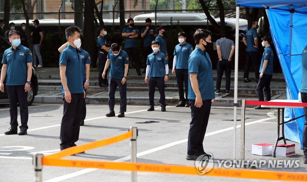资料图片:8月19日,在首尔地方警察厅机动本部的筛查点,曾维持光复节集会秩序的警员接受新冠病毒检测。 韩联社