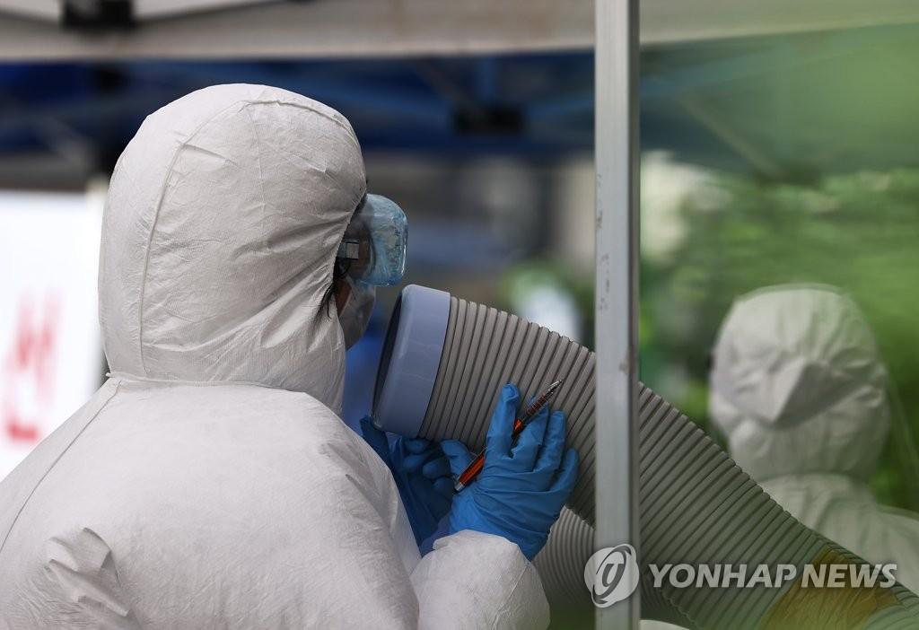 资料图片:8月19日,在设于首尔市钟路区卫生站的筛查诊所,全副武装的医务人员对着冷风机消汗。 韩联社