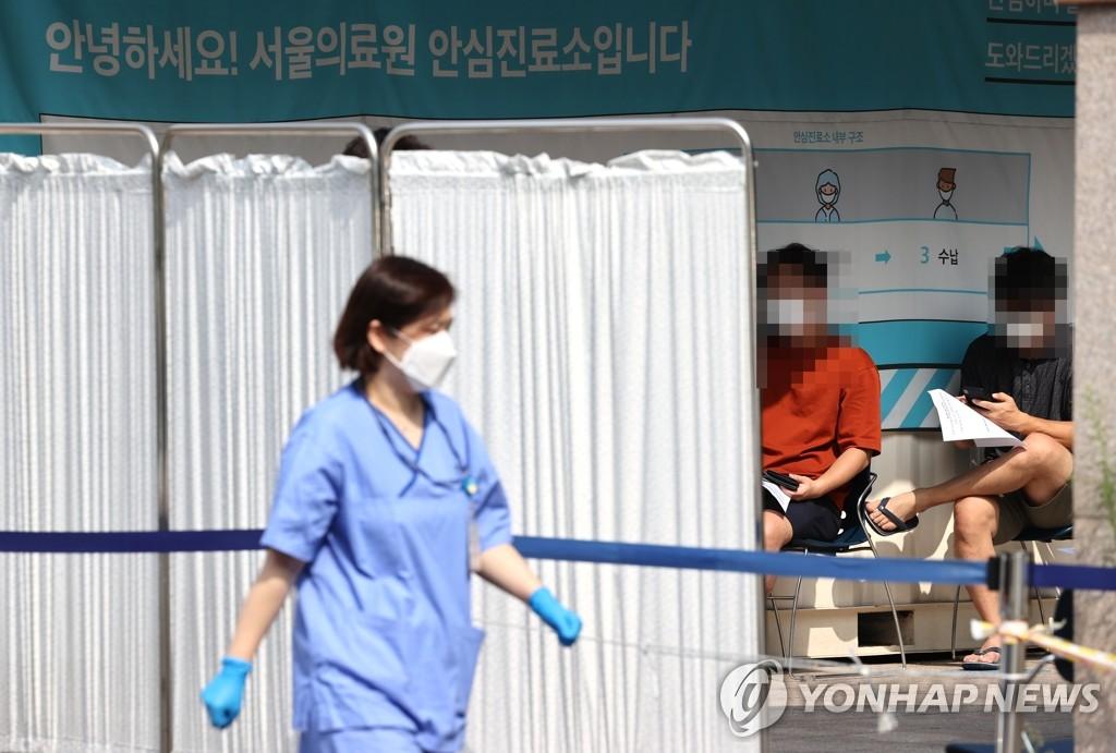 资料图片:8月20日,在首尔医疗院筛查点,市民坐着候检。 韩联社