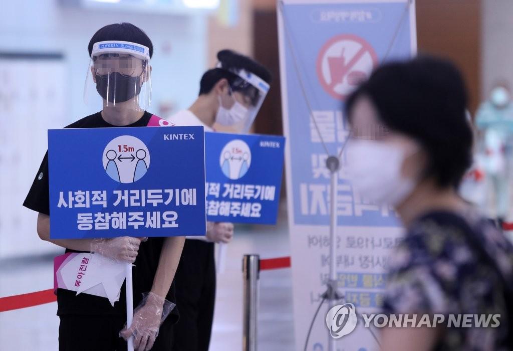 资料图片:8月20日,京畿道高阳市韩国国际会展中心(KINTEX)的工作人员举牌提示观众保持社交距离。 韩联社