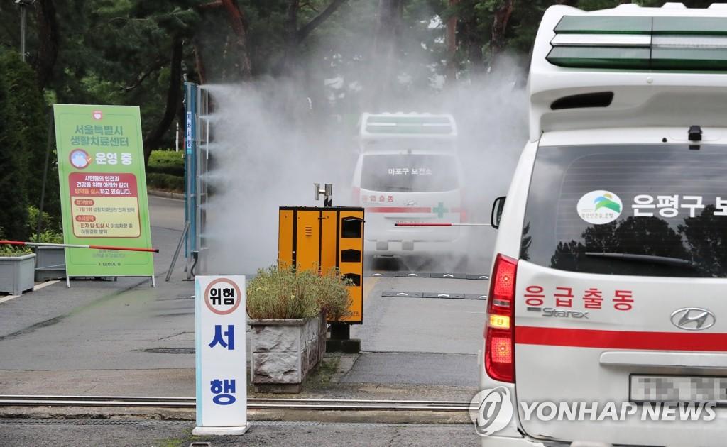 资料图片:8月21日下午,在设有首尔市生活治疗中心的泰陵运动员村,载有新冠病人的救护车陆续到达。 韩联社