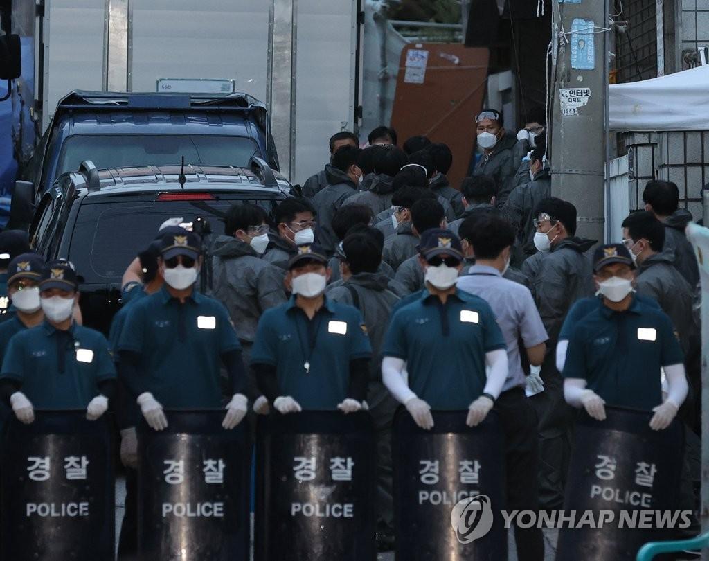 """8月21日,在首尔城北区,警察们手持护盾准备对近期引发大规模群聚性新冠感染的""""爱第一""""教会进行搜查。 韩联社"""