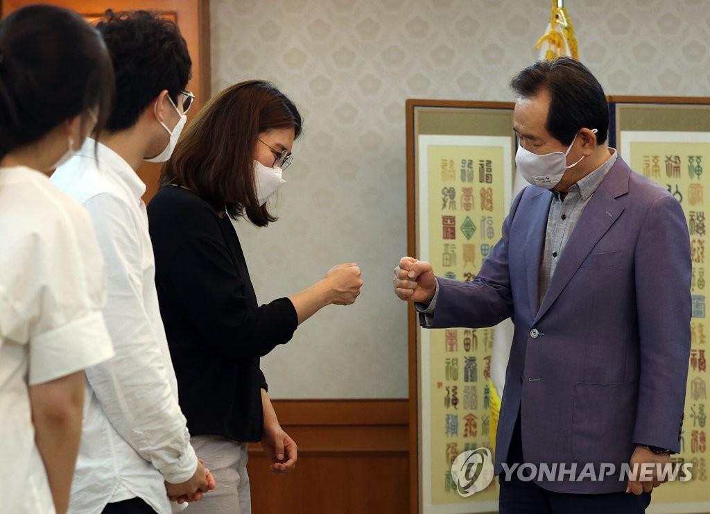 """8月23日,在首尔政府中央办公楼,丁世均(右)与大韩实习医生协会代表团在座谈前""""碰拳""""致意。 韩联社"""