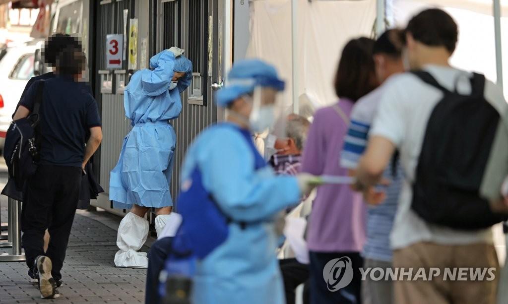 资料图片:市民们在位于首尔市城北区卫生站的筛查诊所内排队待检。 韩联社