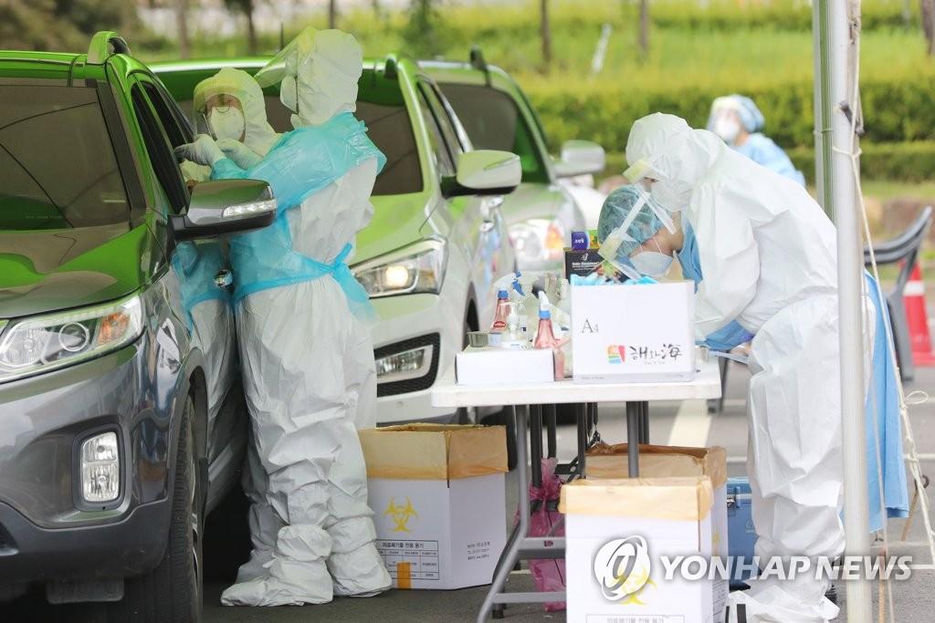 资料图片:在一处免下车筛查诊所,医疗人员进行病毒检测。 韩联社