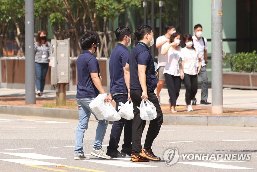 8月25日,在首尔市区,上班族把外卖带回单位。 韩联社