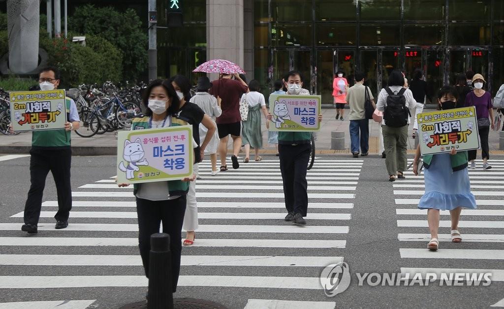 资料图片:8月25日下午,在首尔市阳川区风之街广场,参与WWF(Wear, Wash, Far away)防疫宣传活动的人员手举标语牌,呼吁人们戴口罩、勤洗手、保持距离。 韩联社