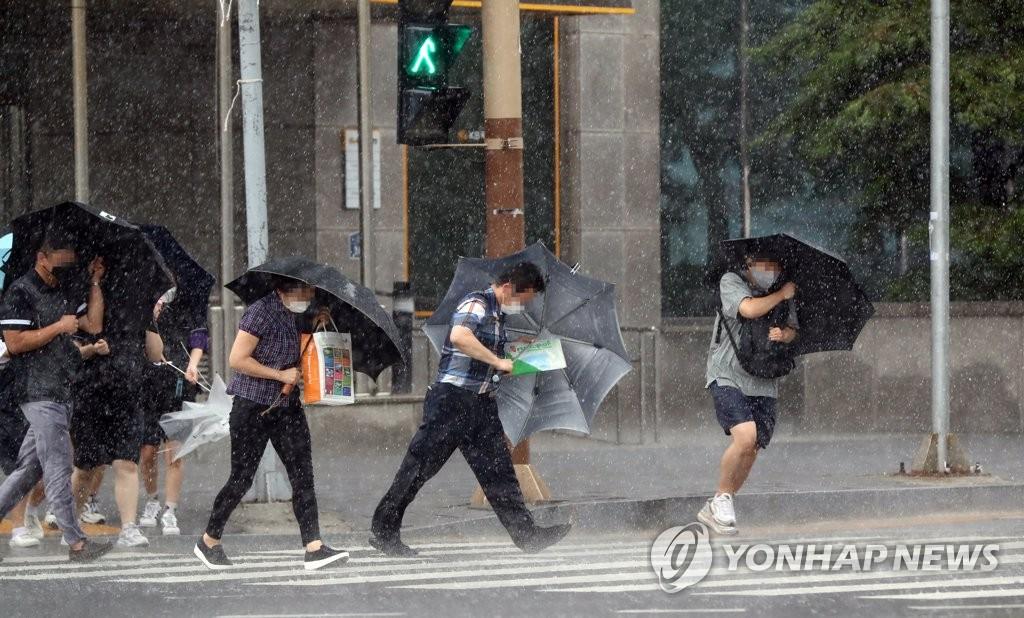"""8月26日,在全罗南道木浦市木浦火车站前的一处人行横道,行人们撑伞冒雨前行。受台风""""巴威""""影响,木浦市遭遇强风暴雨天气。 韩联社"""
