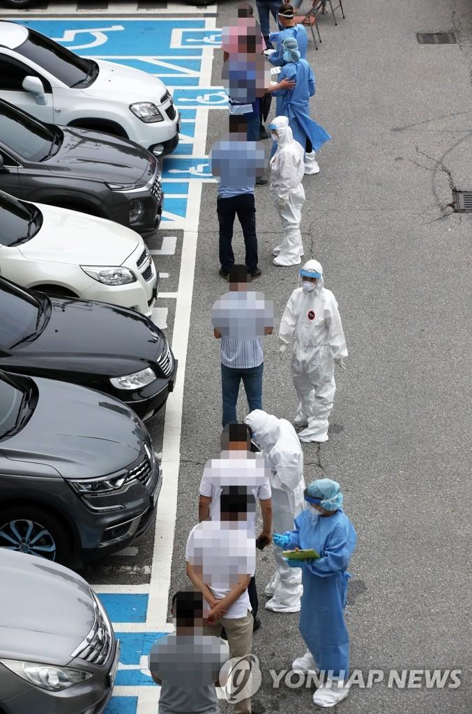 资料图片:8月27日,在光州市东区卫生站筛查诊所,市民们排队等待接受新冠检测。 韩联社