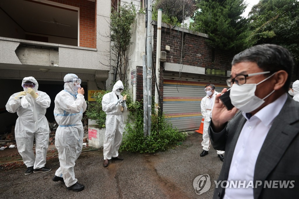 """9月2日下午,首尔警察厅智能犯罪搜查队警员身穿防护服对首尔城北区""""爱第一""""教会牧师全光焄家宅进行扣押搜查。 韩联社"""