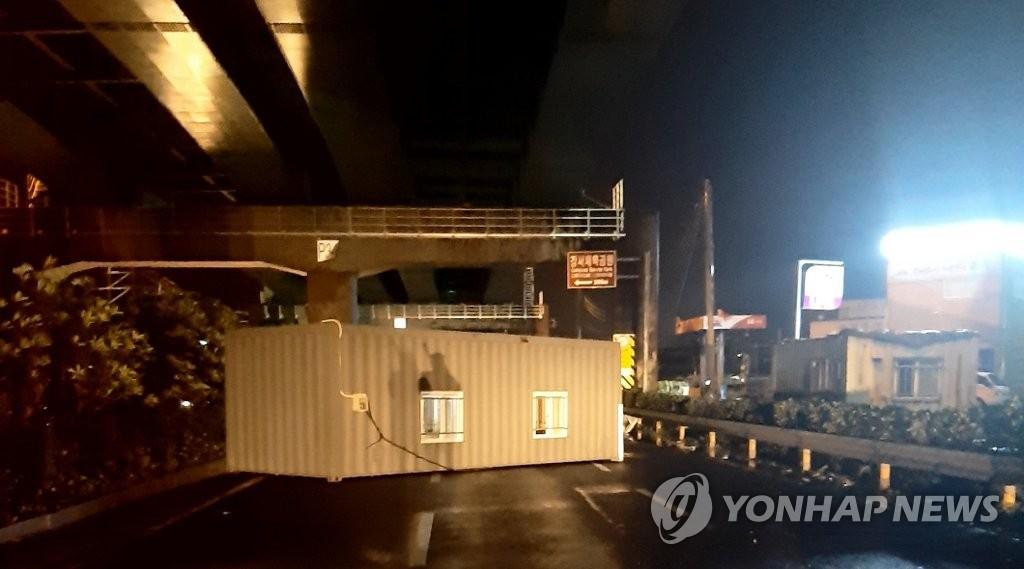 9月3日,在釜山市江西区一条公路上,一个集装箱被强风掀翻。 韩联社/釜山警察厅供图(图片严禁转载复制)